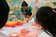 Teacher and children are cutting fruit together