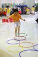 A child is walking over the hula hoops