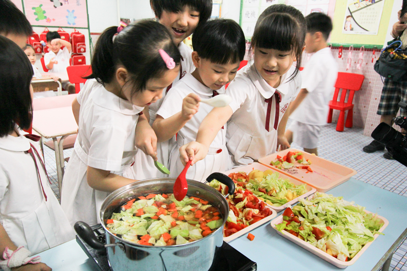 Children are cooking vegetables soup