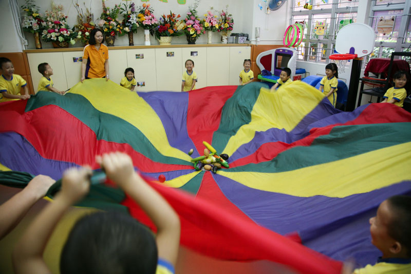 Children are playing rainbow parachute games